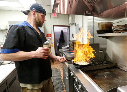 Michael Deichsel sautees onions Wednesday, May 13, 2020 at Bench Warmers in Fond du Lac, Wis. Deichsel co-owns the Scott Street bar and grill with his wife, Sarah.
