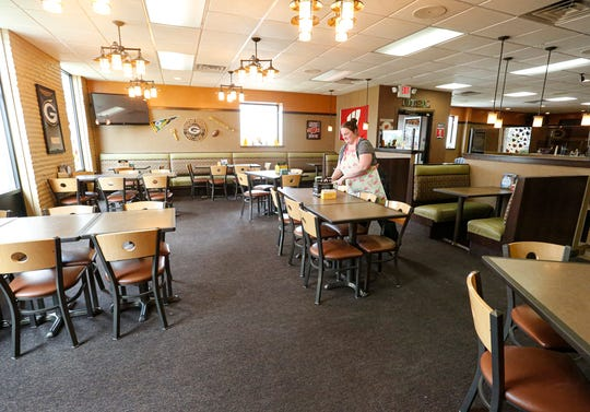 Sarah Deichsel sets out table caddies Wednesday, May 13, 2020 at Bench Warmers in Fond du Lac, Wis. Deichsel co-owns the Scott Street bar and grill with her husband, Michael.