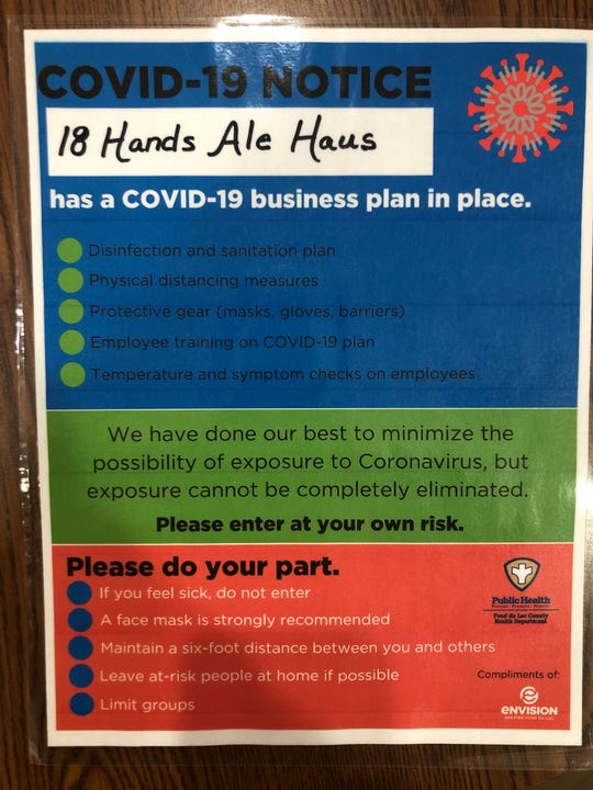 A sign from the Fond du Lac County Public Health Department and Envision Greater Fond du Lac which states 18 Hands Ale Haus has a business plan in place for the coronavirus, and customers should check their symptoms before coming in.