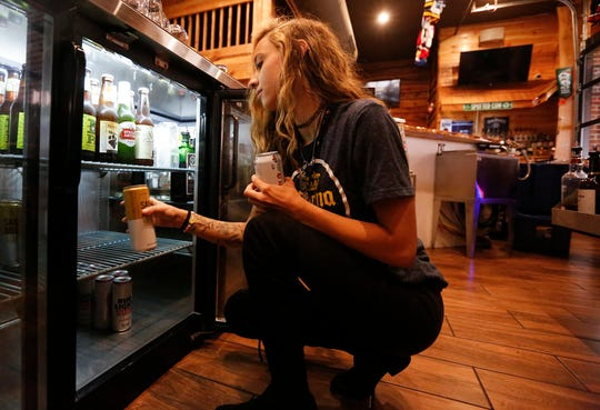 """Bartender Kylee Gibson stocks beer coolers Thursday, May 14, 2020 at Top Shelf Bar and Grill in Fond du Lac, Wis. The restaurant/bar started preparing to open the day after hearing the Wisconsin Supreme Court's decision to strike down Governor Tony Evers extension to the """"safer at home"""" order which closed many Wisconsin businesses."""