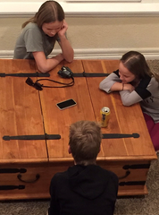 """Hannah Skalicky, Kate Skalicky and Paul Skalicky sit around a cellphone listening to their neighbor, Sheri Carmon, read from """"The Mysterious Benedict Society."""""""