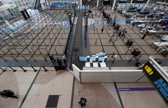 Empty lanes lead to the south security checkpoint in the main terminal of Denver International Airport as it gets back to life with the easing of restrictions to check the spread of the new coronavirus Wednesday, May 13, 2020, in Denver. (AP Photo/David Zalubowski)
