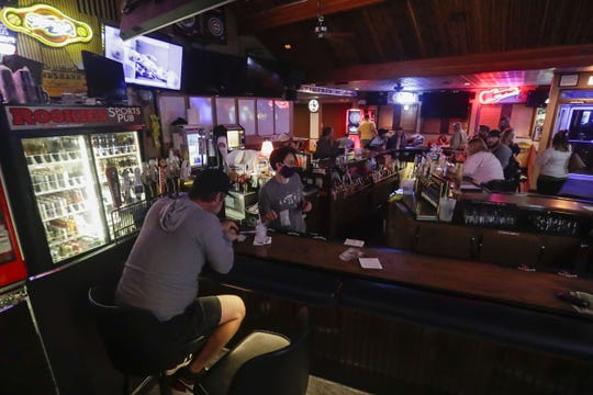 Patrons sit around the bar on Wednesday, May 13, 2020, at Rookies Sports Pub in Stevens Point, Wis. Establishments across the state have been cleared to reopen after the state Supreme Court overturned Governor Tony Evers' safer-at-home order on Wednesday.