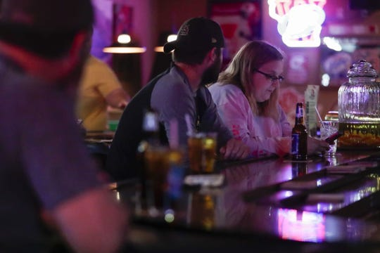 Amanda Slagle checks her phone at the bar on Wednesday at Rookies Sports Pub in Stevens Point. Establishments across the state reopened after the state Supreme Court overturned Governor Tony Evers' safer-at-home order.
