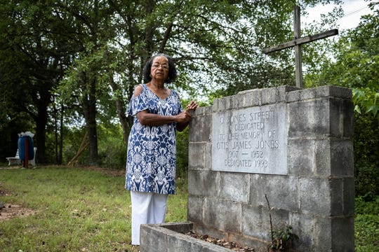 Charity Jones, 77, who lives in the New Washington Heights neighborhood of Greenville, stands by a memorial for her father on Jones Street Thursday, May 14, 2020, which was named after him when it was constructed.