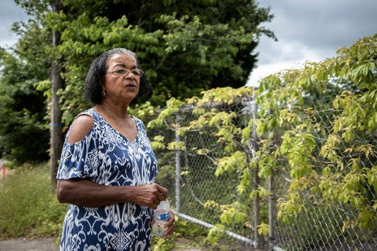 Charity Jones, 77, stands at one of the entrances to the former Washington High School in the New Washington Heights neighborhood of Greenville where Jones lives, Thursday, May 14, 2020.
