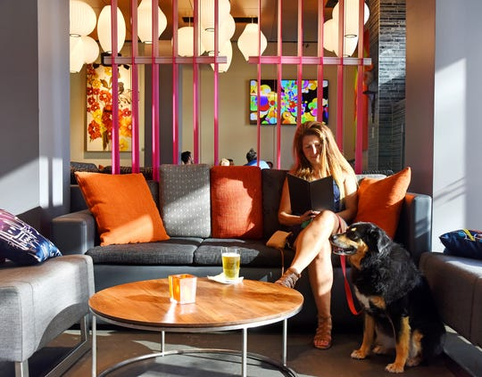 Lizette Pirtle sits with her dog Star at the WXYZ Bar at the Aloft Hotel in downtown Greenville.