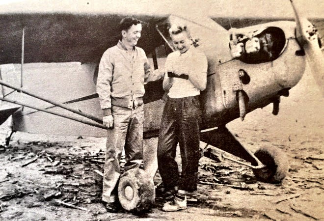 "Don Davis, long-time operator of the Henderson City-County Airport, was 16 years old and had only two weeks of lessons under his belt  before he soloed and received his student pilot license May 18, 1945. He is shown here with instructor Virginia ""Gini"" Stover, who is signing the license. This photo first appeared in The Gleaner of May 20, 1945. The grasss air strip operated from April 1945 to 1949. It lapsed until late 1957 and a new paved runway was dedicated Aug. 30, 1958, under the auspices of the newly formed Henderson City-County Air Board."