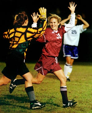 Henderson County back Amy Wilson gets a running high-five from goalkeeper Natalie Taylor after the Lady Colonels advanced to the 1997 regional championship game with a 1-0 win over Bowling Green.