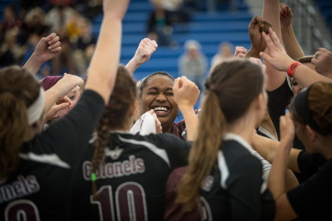 Henderson County's Coach Ashley Robinson and the rest of the Lady Colonels celebrate after winning the 2015 state quarterfinal match against Southwestern at the Kentucky High School girls volleyball championship in Louisville.