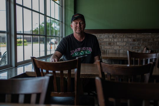 "Dawson's on Main owner Chris Hill sits at an empty table inside his Speedway, Ind., restaurant on Thursday, May 14, 2020. ""Our servers have been here for a long time and they become family,"" he said. ""When you don't see them it's disappointing."" Hill was able to partly keep his staff but others had to be let go due to money issues caused by the coronavirus pandemic. ""That's the great unknown moving forward,"" he said. ""How much staff can we bring back? How much staff should we bring back and with outdoor, we don't have the ability to put up tents here. You have to kind of look to the sky to see what that's going to do to staff appropriately."""