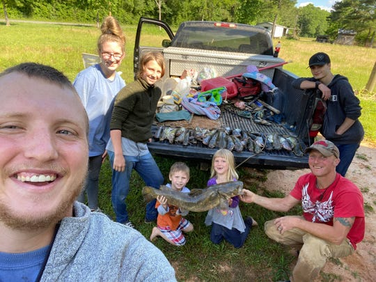 With a tailgate covered with catfish, Colt Mooney (left) and others show how productive fishing in Mississippi creeks can be.