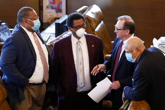 Democratic Sens. Robert Jackson, left, of Marks; Samson Jackson, second from left, of DeKalb; and Joseph Thomas Jr., right, of Yazoo City, confer with Republican President Pro Tem Dean Kirby, of Pearl, as they wait to vote on a coronavirus relief bill for small businesses Wednesday at the Capitol in Jackson, Miss.