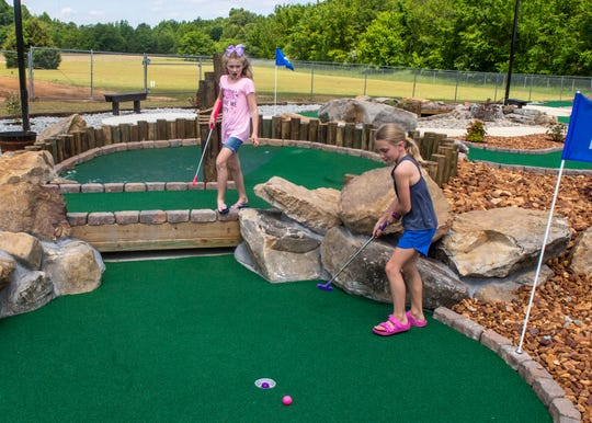 Kylie Cartwright, 9, and Avery-Grace Smith, 9, golf at Fun Zone Jumpers' 3 Rivers Mini Golf course in Jackson, Tenn., on May 15, 2020.
