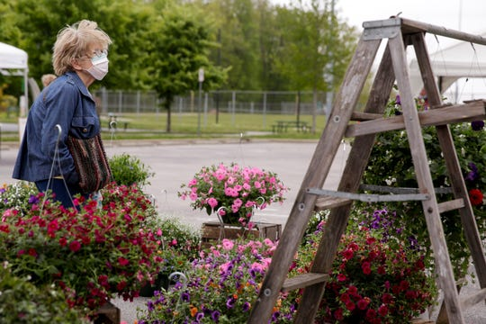 Juanita Linn of Battleground looks through a selection of flower pots at the West Lafayette Farmers Market, Wednesday, May 13, 2020 in West Lafayette.