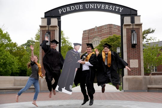 From left, Laura DiPietro, Cameron Curry, Alex Angel and Samuel Dynako pose for graduation photos with a cutout of Purdue University President Mitch Daniels at the Gateway Arch, Wednesday, May 13, 2020 at Purdue University in West Lafayette.