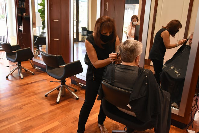 Marci Pagano cuts Tom Britten's hair, as empty chairs help enforce social distancing at Rick's Island Salon and Day Spa on Wednesday. Hair salons and barbershops on Marco Island reopened Monday under new restrictions.