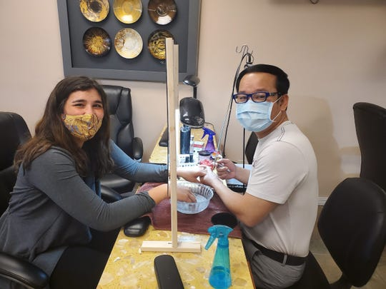 Don Duong, owner of Germantown's Pretty Nails & Spa, is doing Bridget Nelson's nails. Duong, who owns Pretty Nails & Spa with his wife, Lilly, reopened for business at 1 p.m. May 14.