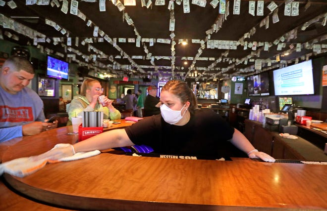 Bartender Carrie Boyle wipes down the bar at A.J. O'Brady's Irish Pub & Grill in Menomonee Falls on Thursday. Patrons were spaced 6 feet apart at the bar and surfaces were cleaned after every patron. In addition, the bar is taking reservations for a limited number of tables available.