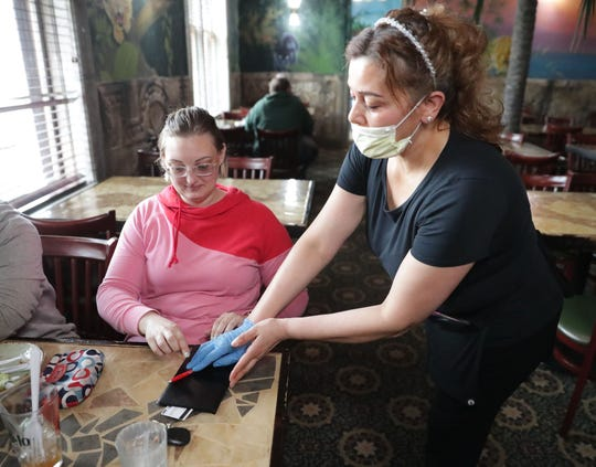 Rosa Tello, wife of Tello's owner, Angel Tello, gives the bill to Jennifer Tews, of Port Washington, after she ate lunch with her daughters at Tello's Mexican Restaurant in Port Washington on Thursday.