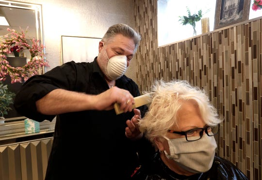 Michael Hoeffler  works on the hair of client Ginger Kraus as he opened his Menomonee Falls salon, Hair Extraordiniar By Michael, Thursday after a state Supreme Court ruling struck down Gov. Tony Evers' safer-at-home order. Hoeffler has booked 12 clients to come, one at a time, into his salon Thursday.