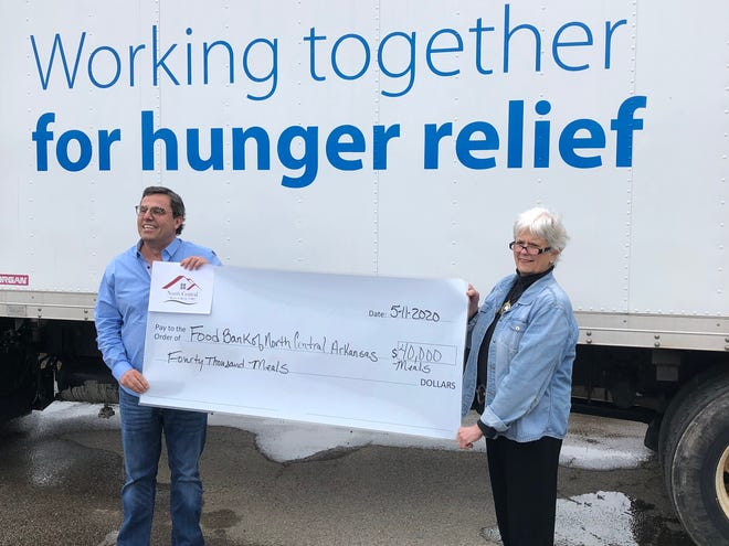Marcia Taylor, President of the North Central Board of REALTORS presents a check to purchase 40,000 meals to Jeff Quick, CEO of the Food Bank of North Central Arkansas.