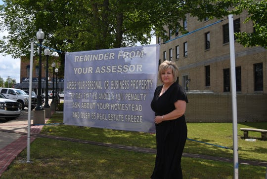 Baxter County Assessor Jayme Nicholson stands next to a sign on the courthouse lawn that reminds passersby that they need to assess their personal or business property with the county.