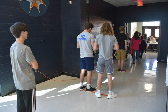Students sign in at Dickson County High School while picking up personal items and picking up graduation tickets on Thursday, May 14.
