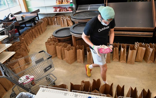 "Stephen DeGrazia of ""The Store"" load bags with groceries, including fresh vegetables, milk and frozen items on Thursday, May 14, 2020. The items are then distributed to the elderly and those in need in Nashville, Tenn."