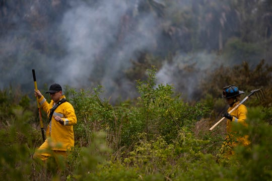 Miami-Dade firefighters Christian Blanco, left, and Matthew Gutierrez, put out spot fires, Thursday, May 14, 2020, off 26th Street in Golden Gate Estates.