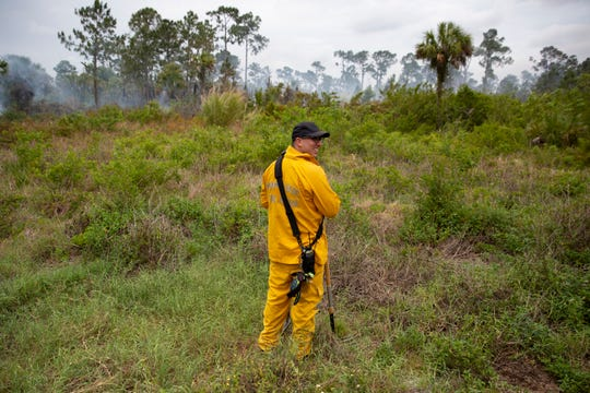 Miami-Dade firefighter Christian Blanco keeps his eye out for spot fires, Thursday, May 14, 2020,  in Golden Gate Estates.