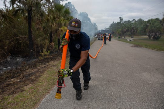 Broward Sheriff Fire Rescue firefighter Rubens Cela moves a hose into position as his team extinguishes spot fires, May 14, 2020, off Everglades Boulevard South in Golden Gate Estates.