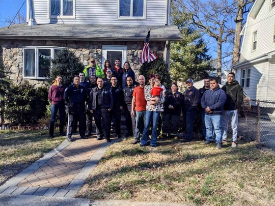 Bergenfield residents Tracey and Brian Rose, standing in center, are outside their home with the first responders who helped the mother give birth to her son Colin during a snowstorm in March 2018.