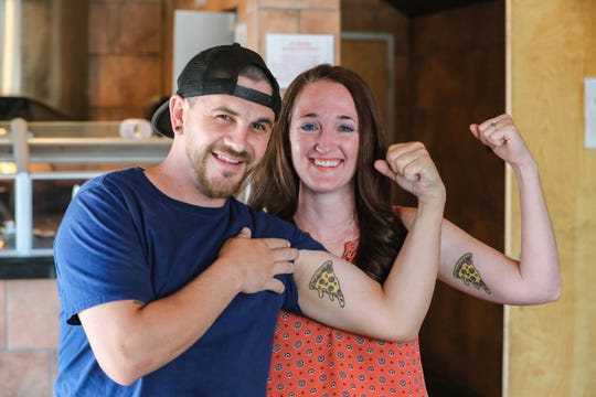 Wade and Jamie McDonald show off their matching pizza tattoos while at King Zah's Pizzeria on Thursday, May 14, 2020. The two met while working at Zefirro's New York Pizzeria on University. Wade purchased the space and plans to open King Zah's soon.
