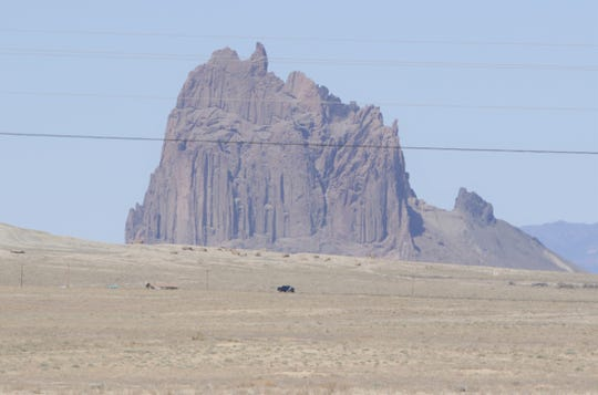 A pickup truck travels on Navajo Route 13 near the Shiprock pinnacle on April 25. Travel has been reduced to essential due to the Navajo Nation being under a weekend curfew to combat the spread of the coronavirus.