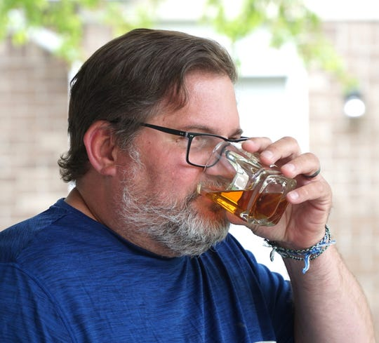 """Scott Linsner has begun a """"Bourbon Bros"""" club from his Canton home where bourbon lovers leave each other gifts of the liquor to enjoy during these stay-at-home days and nights.    Here he takes a sip from a bottle of Eagle Rare bourbon from Kentucky."""