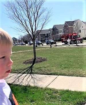 A child watches the procession of emergency vehicles pass his house on his birthday.