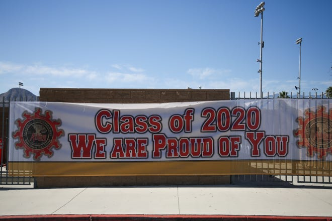 A banner congratulates seniors at Palm Desert High School  on Thursday, May 14, 2020 in Palm Desert, Calif. Due to the coronavirus pandemic, a typical graduation ceremony was replaced with a drive-thru to pick up caps, gowns, tassels and awards.
