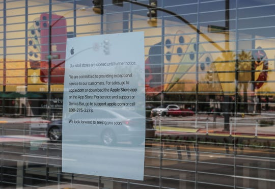 A sign on the window of the Apple Store informs shoppers that they are closed on El Paseo Drive in Palm Desert, May 13, 2020.