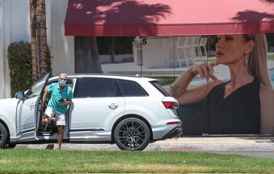 A man wearing a face mask gets out of his vehicle to shop at one of the few businesses that are open on El Paseo in Palm Desert, May 13, 2020.