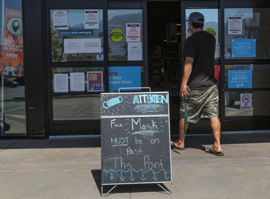 A shopper passes by a sign outside of the entance to PetSmart that informs customers that facemasks are required inside the Palm Springs pet supply store, May 13, 2020.
