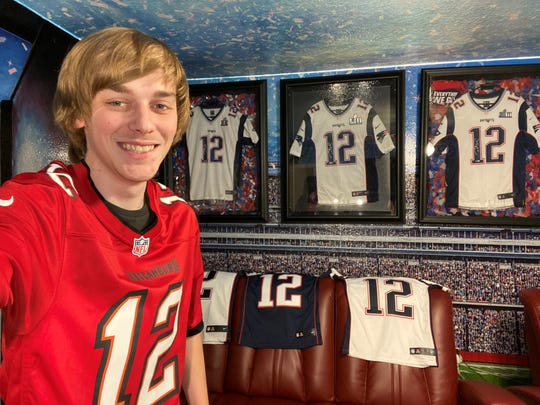 Pensacola YouTube star Logan Thirtyacre poses for a photo in front of his Tom Brady jersey collection while wearing a Brady Tampa Bay Buccaneers jersey.