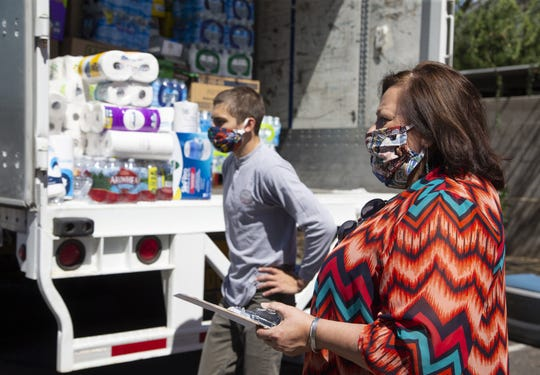Patricia Hibbeler, Phoenix Indian Center CEO, right, and Jake Vercauteren, 22, help take in donations for the COVID-19 relief to the Navajo Nation.