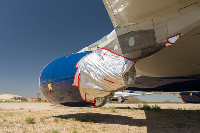 Protective coverings are applied to aircraft parked at Pinal Air Park near Marana. Airlines have been sending more jetliners to the facility as traffic has declined amid the COVID-19 pandemic.