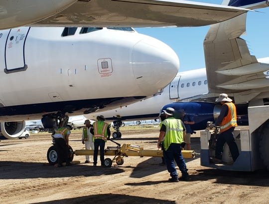 Workers begin the process of preparing a jet aircraft for storage at the Pinal Air Park near Marana, where airlines are sending planes idled by the drop in traffic due to the COVID-19 pandemic.