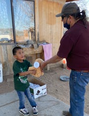 Bruce Plummer gives a teddy bear to a boy in a community on the far eastern edge of Navajo lands in early May while delivering food and water to 160 families who haven't been able to access aid during the COVID-19 pandemic.