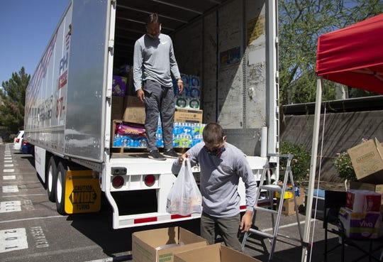 Hank Hibbeler, 22, left-in truck, and Jake Vercauteren, 22, help separate and load a truck at the Phoenix Indian Center for the COVID-19 relief to the Navajo Nation.