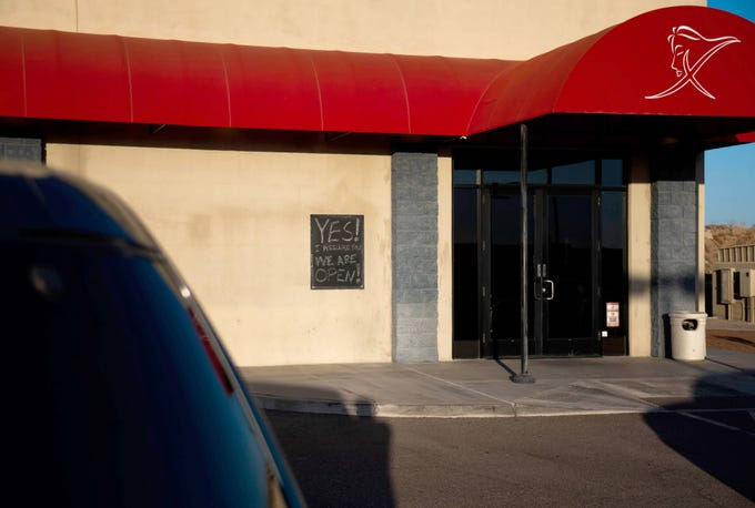 A sign tells customers that Xplicit Showclub, a strip club in Glendale, is open on May 13, 2020.