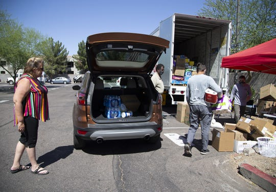 Mary Cassellius, of Peoria, left, drops some donations at the Phoenix Indian Center for the COVID-19 relief to the Navajo Nation.