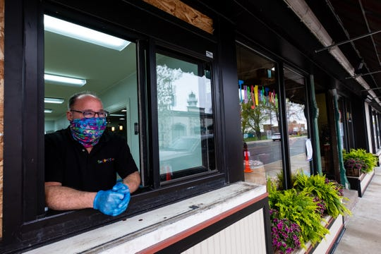 Todd May, owner of The Sweet Tooth in Marine City, poses for a portrait in the newly-constructed walk-up window Thursday, May 14, 2020, in Marine City. The window is being installed in the store to allow customers to place and pick up orders without having to enter the store.